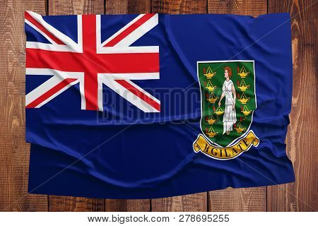 Flag Of British Virgin Islands On A Wooden Table Background. Wrinkled Flag Top View.