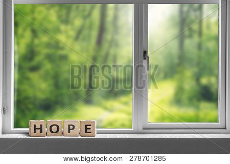 Hope Sign In A Window Sill With A View To A Green Forest In Sunlight