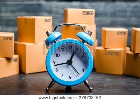 Cardboard Boxes And A Blue Alarm Clock. Time Of Delivery. Limited Supply, Shortage Of Goods In Stock