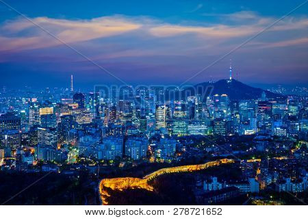 Seoul downtown cityscape illuminated with lights  in the evening view from Inwang mountain. Seoul, South Korea.