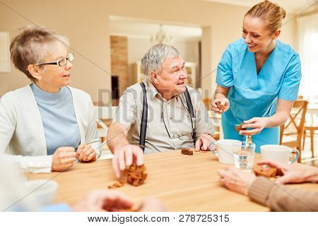 Nursing woman cares for senior couple couple at leisure in retirement home