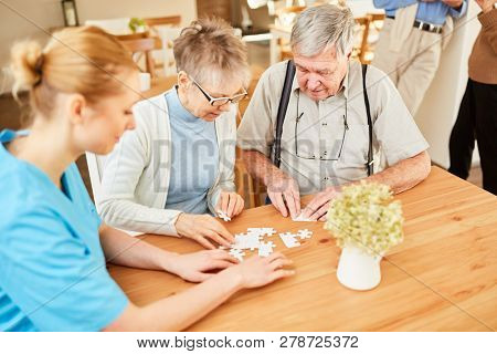 Senior couple playing puzzle with care at retirement home or nursing home