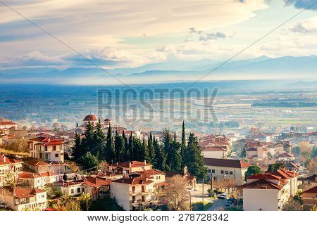 Greek Town Evening Panorama With Red Roof Houses, Valley And Mountains In The Background, Kalambaka,