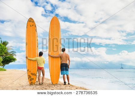 Beach surfers watching waves. Surfing lifestyle. Two people couple standing with longboards on hawaii Kaanapali beach after surf class. Fun sport on Maui summer vacations. USA travel.