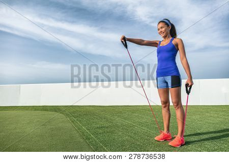 Fitness resistance training with elastics bands woman doing elastic workout outside in summer background. Asian girl pulling up band for shoulder strength. Shoulder front raise exercise.