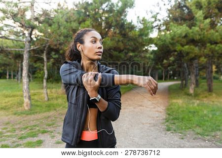 Portrait of attractive african american woman 20s wearing black tracksuit doing exercises and stretching her body in green park