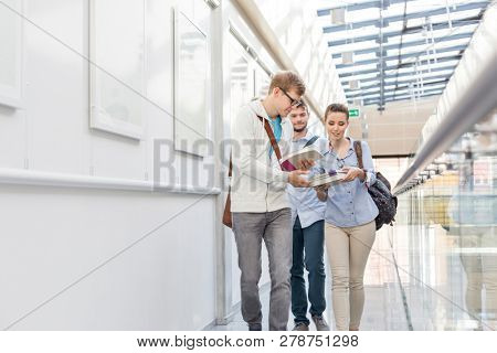 Students exchanging books while walking in corridor at college
