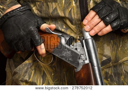 the hands of the shooter in gloves put a cartridge in the shotgun poster