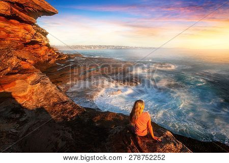 Female Watches The Ocean Wash Up And Cascade Like A Waterfall And Toss And Swirl Around Ocean Rocks