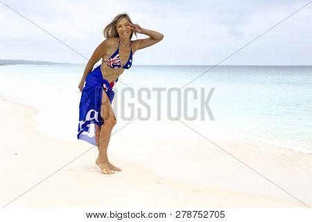 Australian Woman Beach Vibes. Standing On Idyllic Beach Wearing Aussie Flag Sarong And Bikini Patrio