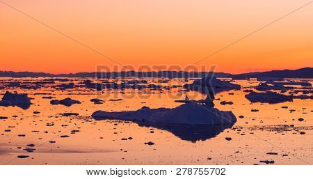 Global Warming and Climate Change - Icebergs from melting glacier in icefjord in Ilulissat, Greenland. Aerial image of arctic nature iceberg and ice landscape. Unesco World Heritage Site.
