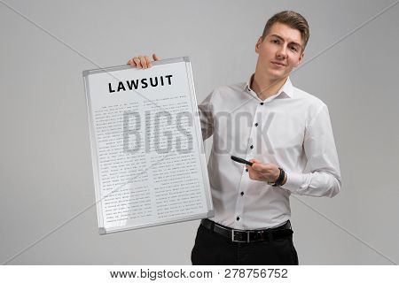 Young Man Holding A Poster With The Inscription Lawsuit Isolated On A Light Background