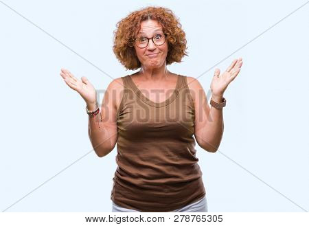 Middle age hispanic woman wearing glasses over isolated background clueless and confused expression with arms and hands raised. Doubt concept.