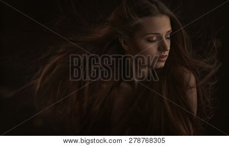 Portrait Of Beautiful Woman With Long Red Hair Isolated Over Dark Background