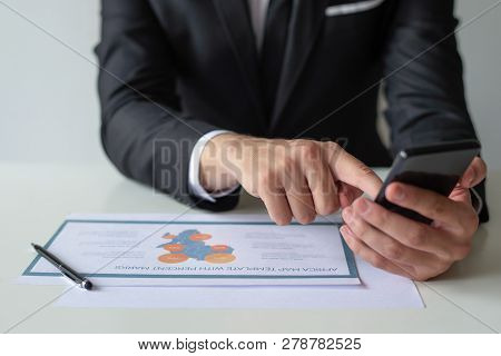 Closeup Of Man Working With Diagram And Browsing On Smartphone. Businessman Sitting At Office Table.