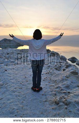 A Girl Raising Her Hands Feeling Free, Spirituality, Enjoying Sunrise. Sunrise Over The Dead Sea Sho
