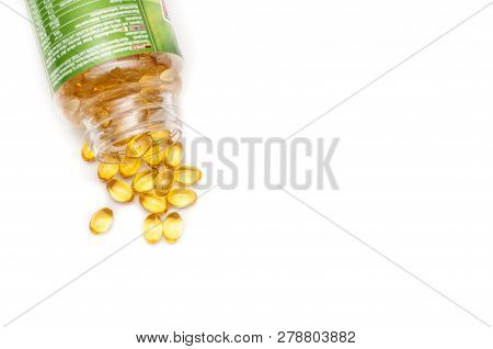 Omega 3 Fish Oil Capsules Spilled From A Plastic Bottle On A White Background. Medical Food Suppleme