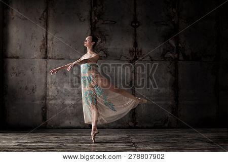 Young Beautiful Ballet Dancer In Beige Dress Posing On Pointes Over Dark Grunge Background