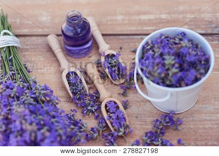 Top View Of A Bowl And Wooden Spoons With Fresh Lavender Flowers, Lavender Essential Oil And A Bouqu