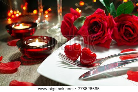 Festive table place setting for Valentines day dinner with red roses and burning candles