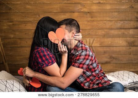 Romantic Couple Sitting On A Sofa In A Loving Embrace Kissing As They Hold Up A Red Paper Heart On W