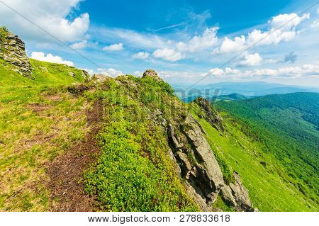 Rocky Edge Of A Grassy Hillside. Mountain Ridge In The Distance. Wonderful Summer Weather. Fleecy Cl
