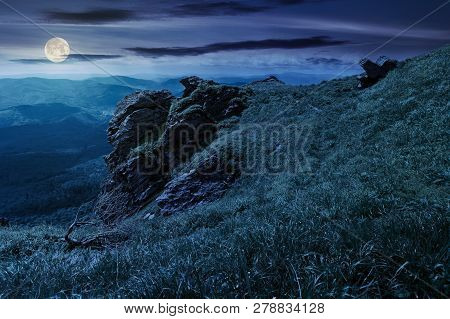 Rocky Formation On A Grassy Hillside At Night. Path Among The Grass To The Boulders. Beautiful Mount