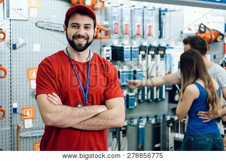 Confident Smiling Salesman On Foreground In Power Tools Store. Guy Is Ready To Help Clients On Backg