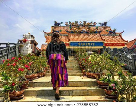 Guan Im Sutham Temple, Kanchanaburi, Thailand - May 19th, 2017: A young female traveler walking up the steps towards the Guan Im Sutham Temple in Kanchanaburi, Thailand.  The temple is a beautifully coloured buddhist chinese temple very popular