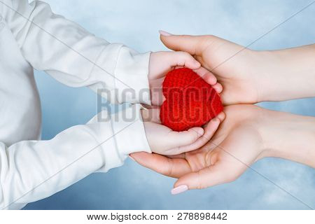 A Closeup Of Child And Adult Female Hands Are Holding A Small Red Heart Together. The Concept Of Clo