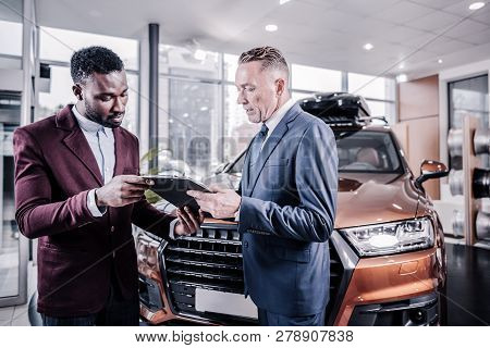 Sales Manager Giving His Client Documents Before Buying Car
