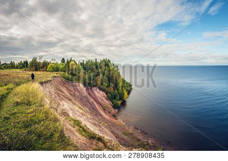 Autumn Landscape. High Cliff On Lake. A Girl Walking On The Edge Of A Cliff.