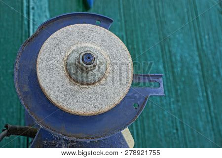 One Old Gray Stone Grinding Wheel On A Metal Machine Against A Green Wall