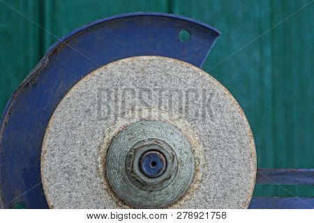Gray Stone Grinding Wheel On A Metal Machine Against A Green Wall