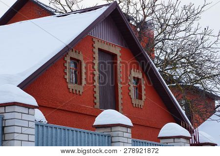Attic Of A Red Country Barn With A Door And Windows And White Snow On The Roof Behind The Fence