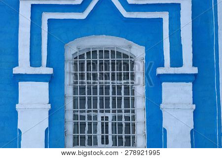 Old Window Behind Iron Bars On A Brick Blue White Wall