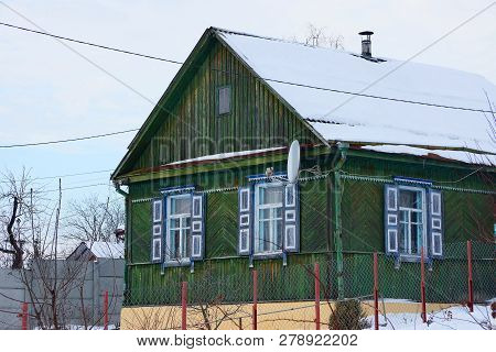 Part Of An Old Green Wooden Farmhouse With Windows And A Roof Under The Snow