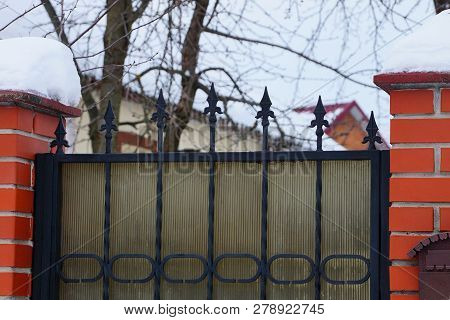 Black Sharp Iron Bars On The Metal Gates And Part Of A Brick Fence In White Snow