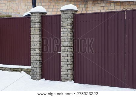 Part Of A Private Brown Iron Fence And A Closed Gate In White Snow Outside