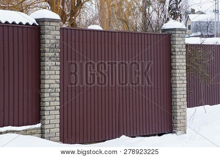 Part Of A Private Brown Metal Fence And A Closed Gate In White Snow Outside