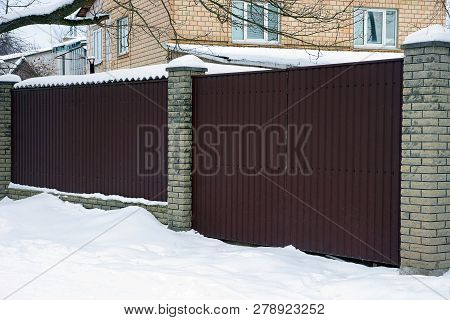 Part Of A Private Brown Metal Fence And A Closed Door In White Snow Outside