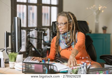 Confident Woman With Drealocks Working At Her Desk