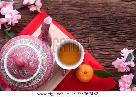 Wood Table With Cup Of Tea And Cherry Blossom, Chinese New Year Celebration Background, Top View.