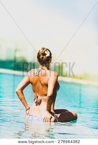 Young Brunette Woman Relaxing By The Side Of The Infinity Pool