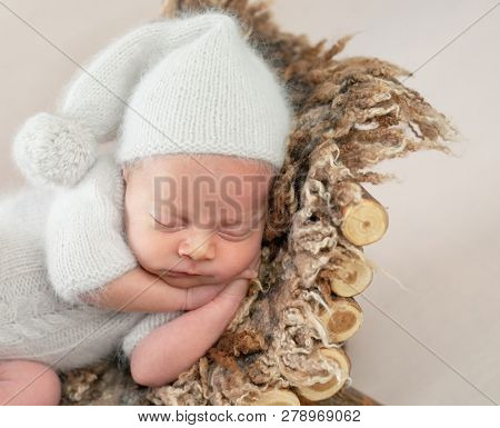 Cute little baby in white hat and knitted suit sweetly sleeping on furry brown pillow