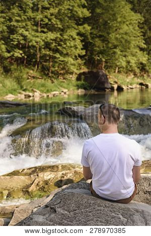Man In White T-shirt Sitting On The Bank Of The River Against The Background Of A Waterfall And Gree