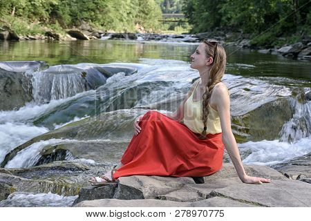 Beautiful Long-haired Girl In A Red Skirt Sitting On A Rock On A Background Of Mountain River Cascad