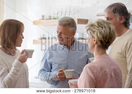 Mature friends holding drinks while talking in living room at home