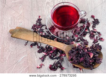 Hibiscus Tea In A Glass Cup On A Wooden Table Among The Rose Petals And Dry Tea. Vitamin Tea For Col