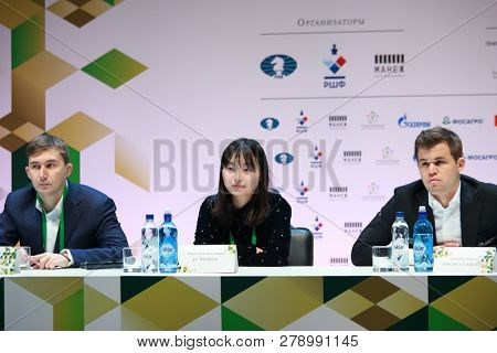 ST. PETERSBURG, RUSSIA - DECEMBER 25, 2018: World Chess Champions Ju Wenjun, China (center) and Magnus Carlsen, Norway (right), and Vice-Champion Sergey Karjakin, Russia on the press conference